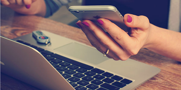 view of woman with manicured hands (no face or body) holding phone while on laptop
