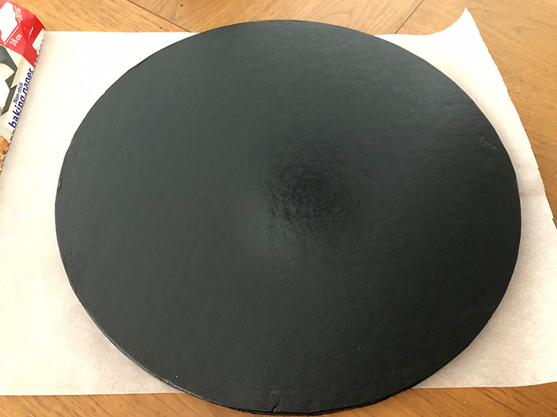 black 16inch/40cm cakeboard placed on greaseproof paper