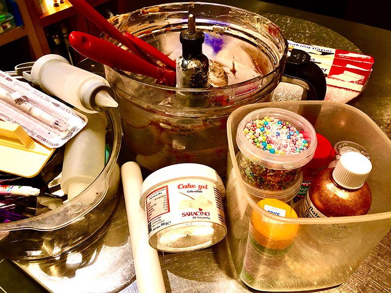 Collection of cake decorating items assembled on counter ready for creation of music themed cake