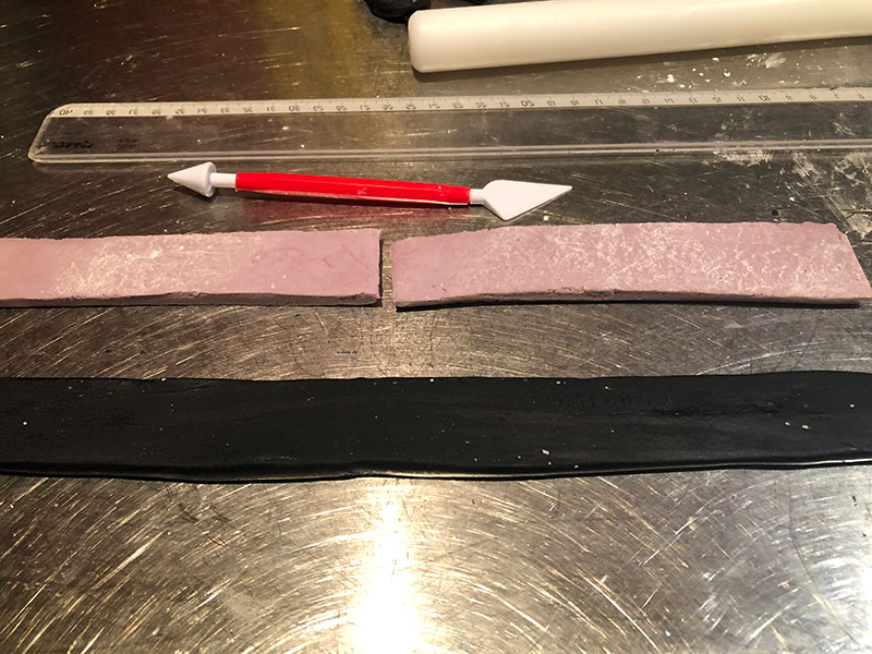 strips of rolled out lilac and black fondant plus cutting tool and rolling pin visible in background