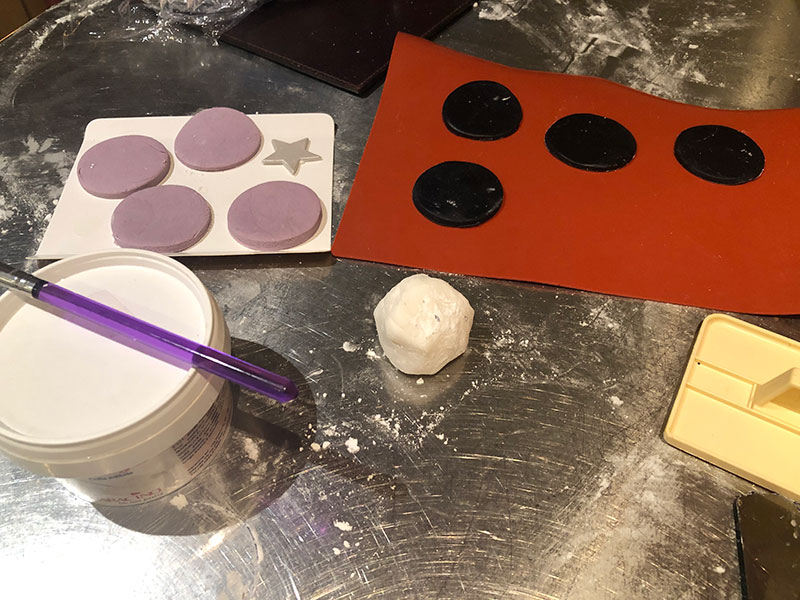 flat purple-and-black-discs-of fondant for creation of headphones on music themed cake