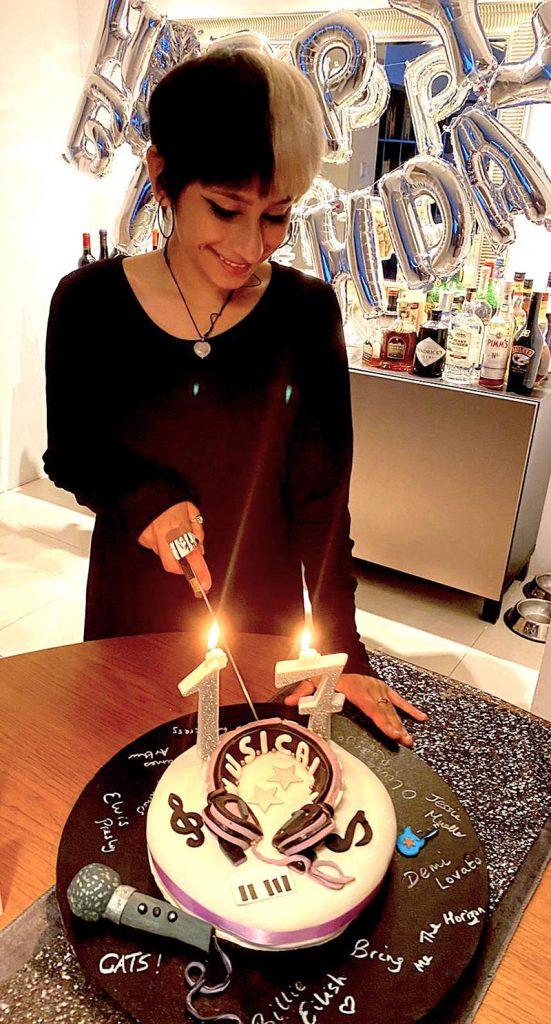 Birthday girl cutting her music themed cake on her 17th birthday