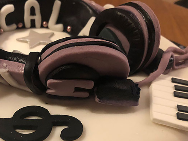 close up of headphones on top of music themed cake